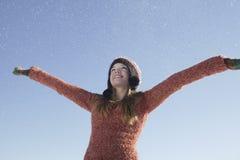 Muchacha que lleva la ropa caliente con los brazos extendidos en nieve Imagenes de archivo