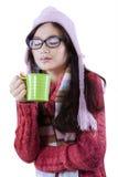 Muchacha que lleva la ropa hecha punto y que bebe el café Imagenes de archivo