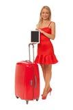 Muchacha que lleva la tableta roja de la tenencia del vestido con la maleta grande Fotos de archivo libres de regalías