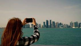 Muchacha que lleva las fotos los rascacielos con smartphone en Doha Qatar metrajes