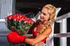 Muchacha que lleva los guantes rojos que se sientan en la esquina del ring de boxeo Fotos de archivo
