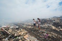 Muchacha que lleva a su amigo a través del humo en la descarga de basura Imagenes de archivo