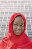 Muchacha que lleva un pañuelo rojo en la calle, trece años Foto de archivo libre de regalías