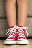 Muchacha que lleva un par de zapatillas de deporte rojas Fotos de archivo
