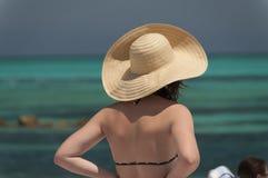 Muchacha que lleva un sombrero que mira el océano. Imagen de archivo