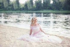 muchacha que lleva un vestido bohemio largo que se sienta en la playa en un fin de semana de las vacaciones Una señora sola se si imagen de archivo