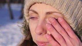 Muchacha que llora, limpiando los rasgones, al aire libre en invierno, cámara lenta, muy cerca para arriba almacen de video