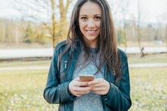Muchacha que manda un SMS con su teléfono Fotografía de archivo libre de regalías