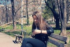Muchacha que manda un SMS en el teléfono elegante Imagenes de archivo
