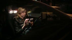 Muchacha que manda un SMS en el teléfono elegante en coche en la noche metrajes