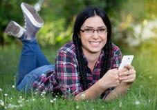 Muchacha que manda un SMS en el teléfono elegante en hierba Fotografía de archivo libre de regalías