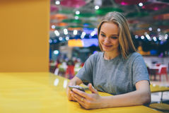 Muchacha que manda un SMS en el teléfono elegante en una terraza del restaurante con un fondo unfocused Fotografía de archivo