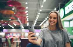 Muchacha que manda un SMS en el teléfono elegante en una terraza del restaurante con un fondo unfocused Imagen de archivo libre de regalías