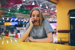 Muchacha que manda un SMS en el teléfono elegante en una terraza del restaurante con un fondo unfocused Fotos de archivo