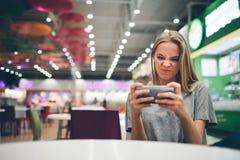 Muchacha que manda un SMS en el teléfono elegante en una terraza del restaurante con un fondo unfocused Imagen de archivo