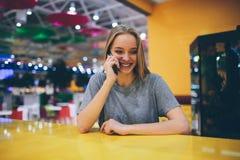 Muchacha que manda un SMS en el teléfono elegante en una terraza del restaurante con un fondo unfocused Fotos de archivo libres de regalías