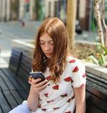 Muchacha que manda un SMS en el teléfono elegante que se sienta en un banco Foto de archivo