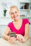 Muchacha que manda un SMS en el teléfono móvil dentro Fotografía de archivo libre de regalías
