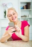 Muchacha que manda un SMS en el teléfono móvil dentro Imagen de archivo libre de regalías