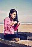 Muchacha que manda un SMS en la playa Imagen de archivo libre de regalías