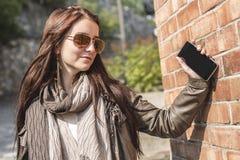 Muchacha que manda un SMS en su teléfono celular con la pared urbana encendido Imagen de archivo libre de regalías