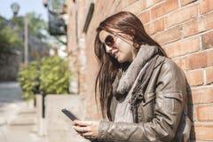 Muchacha que manda un SMS en su teléfono celular con la pared urbana encendido Fotos de archivo