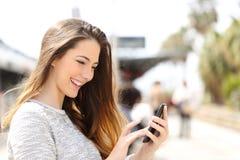 Muchacha que manda un SMS en un teléfono elegante en una estación de tren Fotos de archivo