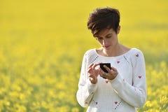 Muchacha que manda un SMS a un mensaje en el teléfono elegante Fotos de archivo