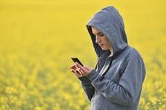 Muchacha que manda un SMS a un mensaje en el teléfono elegante Imagen de archivo libre de regalías