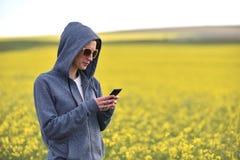 Muchacha que manda un SMS a un mensaje en el teléfono elegante Foto de archivo