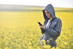Muchacha que manda un SMS a un mensaje en el teléfono elegante Foto de archivo libre de regalías