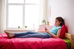 Muchacha que manda un SMS o que juega al juego en smartphone en casa Fotografía de archivo