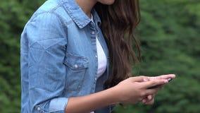 Muchacha que manda un SMS o que usa al teléfono elegante almacen de metraje de vídeo