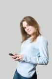 Muchacha que marca en el teléfono celular Fotografía de archivo libre de regalías