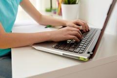 Muchacha que mecanografía en el ordenador portátil en casa Fotos de archivo