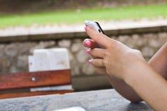 Muchacha que mecanografía en su teléfono Foto de archivo