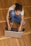 Muchacha que mecanografía en un ordenador portátil que sienta el piso de entarimado Imagen de archivo