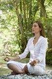Muchacha que medita en Lotus Position By Forest River Fotografía de archivo