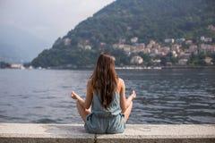 Muchacha que medita por el lago Fotos de archivo libres de regalías