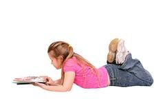 Muchacha que miente abajo leyendo Foto de archivo libre de regalías