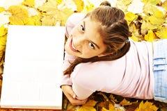 Muchacha que miente abajo libro de lectura con las hojas alrededor Fotografía de archivo libre de regalías