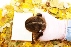 Muchacha que miente abajo libro de lectura con las hojas alrededor Imágenes de archivo libres de regalías