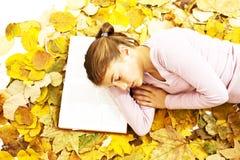 Muchacha que miente abajo libro de lectura con las hojas alrededor Foto de archivo libre de regalías
