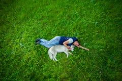Muchacha que miente con su perrito en hierba verde fotografía de archivo libre de regalías
