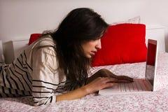 Muchacha que miente en cama con la computadora portátil Fotografía de archivo libre de regalías