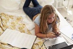 Muchacha que miente en cama usando el smartphone y el ordenador portátil, alto ángulo Imágenes de archivo libres de regalías