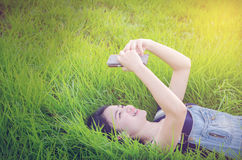 Muchacha que miente en campo de hierba y que usa el teléfono móvil Foto de archivo
