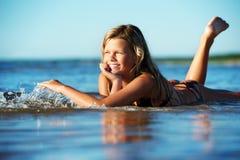 Muchacha que miente en el agua Fotos de archivo