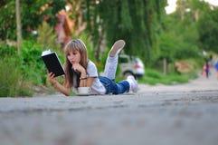 Muchacha que miente en el camino y que lee un libro Foto de archivo