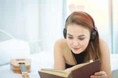 Muchacha que miente en el libro de lectura de la cama y que escucha la música en los auriculares Imágenes de archivo libres de regalías